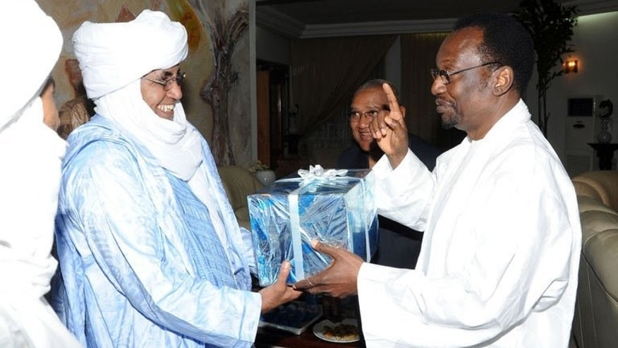 Mali's interim president Dioncounda Traore (R) exchanges gifts with Tuareg leader Ibrahim Ag Assaleh in Bamako on July 21, 2013. Voter registration cards went out in an atmosphere of calm in the northern Malian town where election officials were briefly kidnapped, one of the freed workers told AFP.