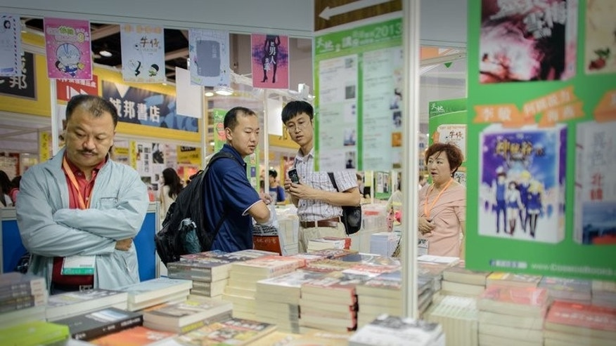 "Visitors browse books displayed at the Hong Kong Book Fair on July 17, 2013. It may be unclear what exactly Beijing means by its aspirational ""China Dream"" slogan, but for banned ""Wild Swans"" author Jung Chang it's a positive step. ""It's good to have a dream,"" she says. ""My dream is to have my books published in China."""