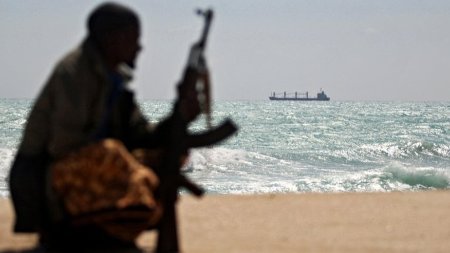 An armed Somali pirate looks out to sea as a cargo ship is seen anchored off the shores of Hobyo on January 7, 2010. On Somalia's pirate coast, more than 50 sailors are being held for ransom in grim conditions, many abandoned by their ship's owner whose willingness to pay to free them sank with their boat.