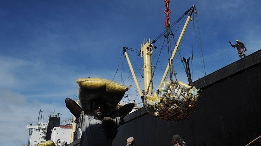 A Somalian porter carries imported goods on his head on April 24, 2013 at the sea port in Mogadishu. On Somalia's pirate coast, more than 50 sailors are being held for ransom in grim conditions, many abandoned by their ship's owner whose willingness to pay to free them sank with their boat.