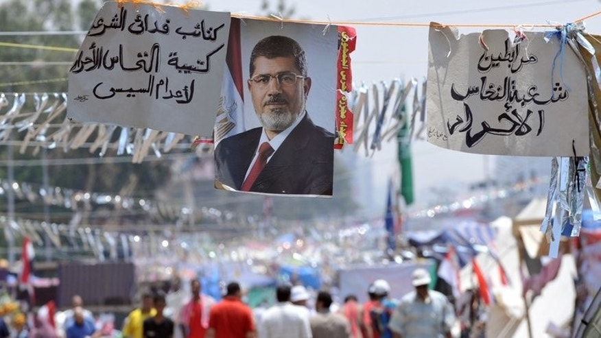 Supporters of Egypt's deposed president Mohamed Morsi walk past his portrait in Cairo on July 23, 2013. Deadly clashes between supporters and opponents of Morsi left 13 people dead, as pressure grew on Egypt's new leaders to release the deposed Islamist president.