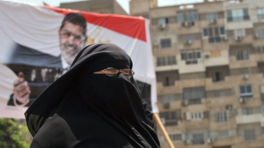 A conservative Muslim Egyptian woman walks past a portrait of deposed president Mohamed Morsi in Cairo on July 23, 2013. Deadly clashes between supporters and opponents of Mohamed Morsi left 13 people dead, as pressure grew on Egypt's new leaders to release the deposed Islamist president.
