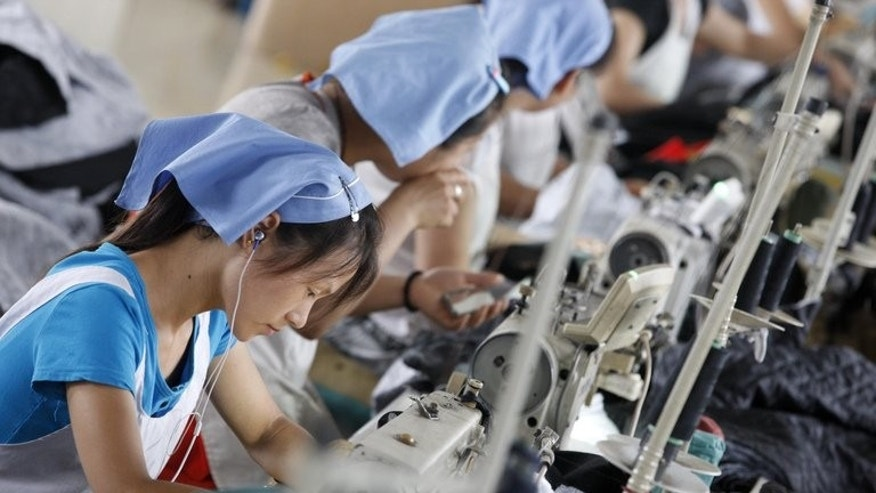 Women work at a clothes factory in Huaibei, north China's Anhui province, July 15, 2013. China's manufacturing activity contracted to a 11-month low in July, an HSBC survey showed Wednesday, the first evidence of the Asian economic giant losing further momentum in the third quarter.
