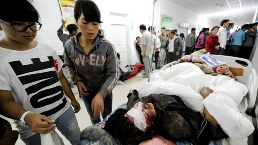 July 22, 2013: Chinese women look at a person injured by an earthquake resting on a bed at a hospital in Minxian county in Dingxi city in northwest China's Gansu province. (AP Photo)