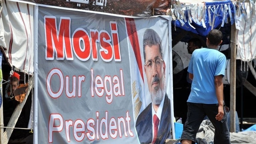 A youth walks past a portrait of deposed president Morsi in Cairo on July 23, 2013. Senior aides held with Morsi since Egypt's army toppled him nearly three weeks ago have asked their families for prison clothes, signalling possible charges, relatives say.