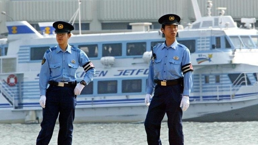 """Japanese policemen patrol the Niigata Port, on June 8, 2003. Japanese police are hunting for a """"haiku poet""""suspected of killing five people in a tiny mountain village."""