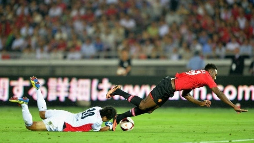 Manchester United forward Danny Welbeck (R) collides with Yokohama Marinos goalkeeper Yuji Rokutan at Nissan Stadium in Yokohama on July 23, 2013. The English champions stumbled to a 3-2 defeat against Yokohama in their second loss in three games under new manager David Moyes.