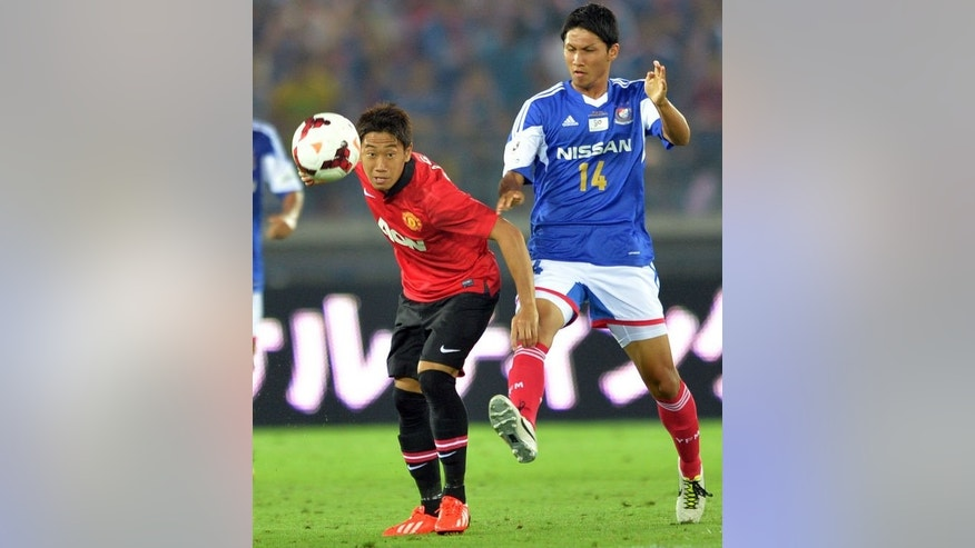 Manchester United midfielder Shinji Kagawa (L) and Yokohama Marinos' Andrew Kumagai fight for the ball at Nissan Stadium in Yokohama on July 23, 2013. The English champions stumbled to a 3-2 defeat against Yokohama in their second loss in three games under new manager David Moyes.