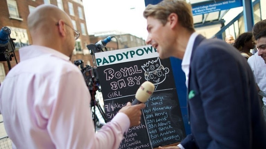 Journalists discuss the odds for the royal baby's name outside St Mary's Hospital in Paddington, central London on July 22, 2013. Prince William and his wife Kate have yet to announce a name for their new newborn son -- but bookmakers have tipped George and James as likely contenders for Britain's new third in line to the throne.