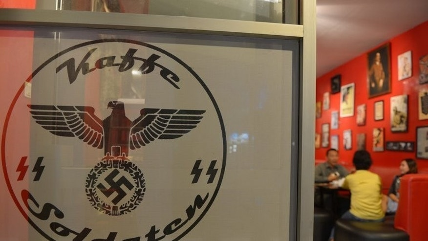 Customers have dinner at the SoldatenKaffee in Bandung, on July 16, 2013. The controversial Nazi-themed cafe in Indonesia will be reopened with a broader World War II theme -- without the swastika symbols but retaining images of Adolf Hitler, according to the owner's lawyer.