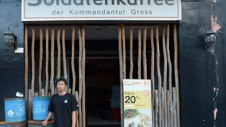 "This picture taken on July 16, 2013 shows owner Henry Mulyana outside his ""Soldiers' Cafe"" in Bandung, Indonesia. The controversial Nazi-themed cafe in Indonesia will be reopened with a broader World War II theme -- without the swastika symbols but retaining images of Adolf Hitler, according to the owner's lawyer."