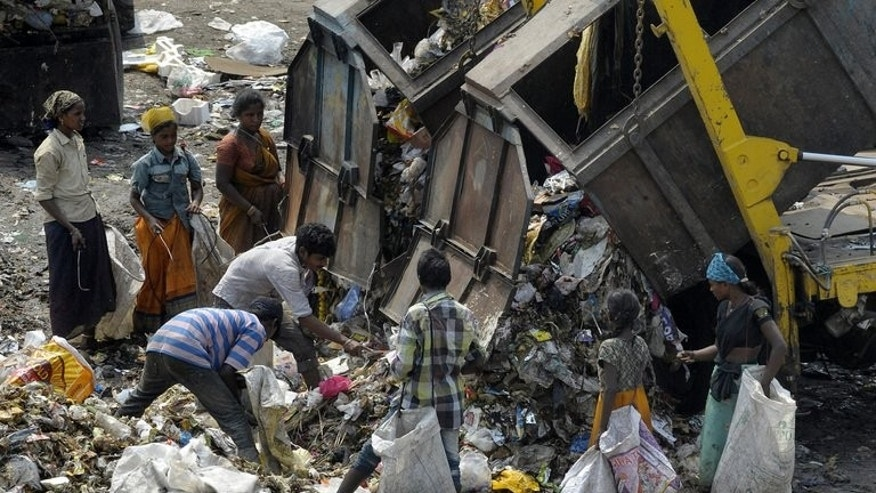 "Indian rag-pickers collect recyclable items at a garbage dump yard in Hyderabad on June 5, 2013. The percentage of Indians living below the poverty line has fallen to 22 percent from 37 percent in just seven years, according to official data released Tuesday, but the figures were dismissed by critics as ""deeply flawed""."