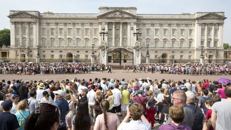 Crowds of tourists gather on the steps of the Queen Victoria Memorial Statue outside Buckingham Palace in central London on July 22, 2013. British companies can expect a temporary boost from the birth of Prince William and Kate's new baby as souvenirs and champagne fly off the shelves and tourists flock to the country, business leaders and analysts said Tuesday.