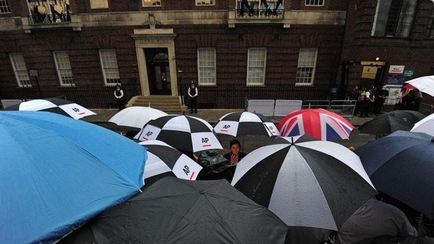 "Members of the media shelter from the rain under umbrellas as they wait for the appearance of Prince William and Catherine, Duchess of Cambridge and their new-born baby boy outside The Lindo Wing of Saint Mary's Hospital in Paddington, west London on July 23, 2013. Astrologers say the future king will be a sensitive Cancerian who could help ""transform"" the royal family."