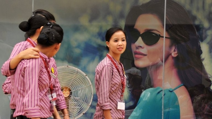 Indian shopping mall employees walk past a billboard in Siliguri on April 15, 2013. Dynamic growth and an expanding middle class are making Southeast Asian consumers among the most confident in the world when it comes to their economic prospects, a survey shows.