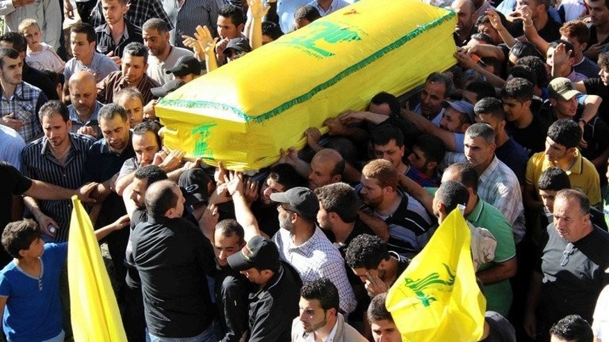 Mourners carry the coffin of a Hezbollah fighter killed in Syria during his funeral procession in the southern Lebanese village of Khiam, on July 5, 2013. The Syrian opposition has welcomed the EU decision to blacklist Hezbollah's military wing and said that leaders of the Lebanese Shiite movement should be put on trial for their role in the Syrian war.