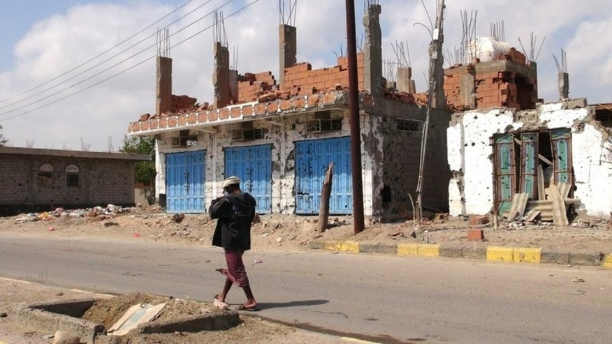 A Yemeni man walks past destroyed buildings in Zinjibar, capital of Abyan province in southern Yemen on December 5, 2012. Yemeni authorities have released a journalist who had been detained for three years on charges of promoting Al-Qaeda, the state news agency Saba reports.