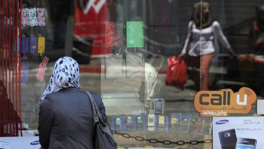 A Palestinian woman checks the display window of a mobile phone shop on Wednesday in the West Bank city of Ramallah. Israel's refusal to give Palestinian mobile companies access to the necessary frequencies for 3G means West Bank residents must sign up with an Israeli company to get mobile Internet, but calling rates are more expensive in the territories.
