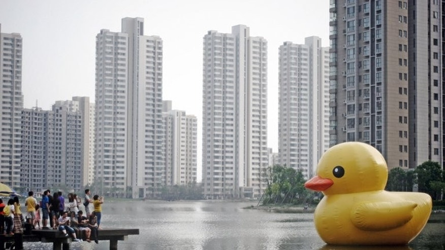 This picture taken on June 1, 2013 shows visitors taking photos of a giant inflatable duck in eastern China's Tianjin. The popularity of a giant inflatable duck afloat in Hong Kong harbour has not gone unnoticed in mainland China, where two copies have been launched in as many days, according to reports on June 1. CHINA OUT AFP PHOTO