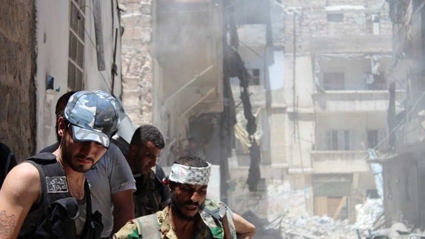 Syrian rebels gather outside a building they blew up in the northern city of Aleppo on July 10, 2013. The International Committee of the Red Cross warns that thousands of Syrian civilians besieged by government and rebel forces alike are in desperate need of aid.