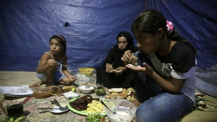 A Syrian refugee widow whose husband died in Homs eats with her daughters in the Lebanese city of Tripoli, July 15, 2013. The International Committee of the Red Cross warns that thousands of Syrian civilians besieged by government and rebel forces alike are in desperate need of aid.