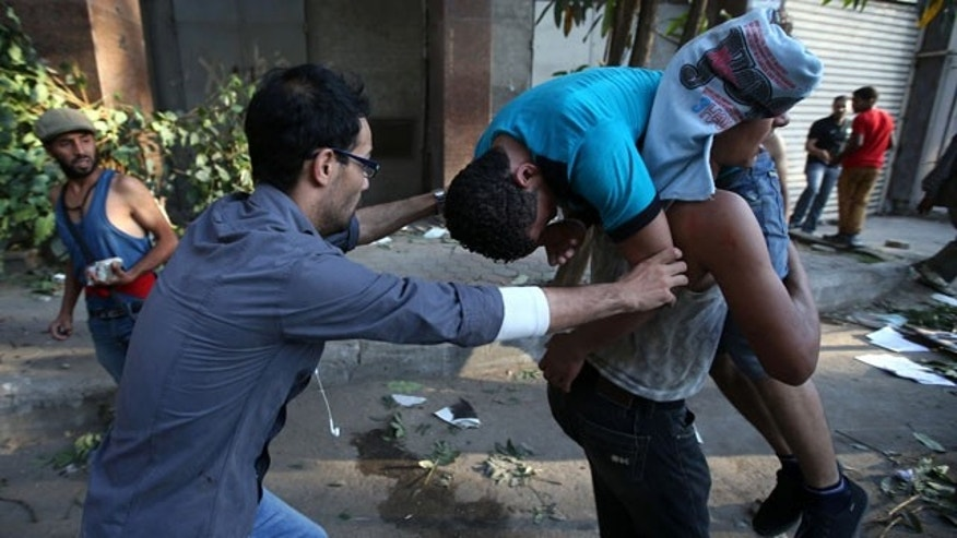 July 22, 2013: Opponents of ousted Egypt President Mohammed Morsi carry their injured friend who was wounded during clashes with Morsi supporters in Cairo. (AP Photo)