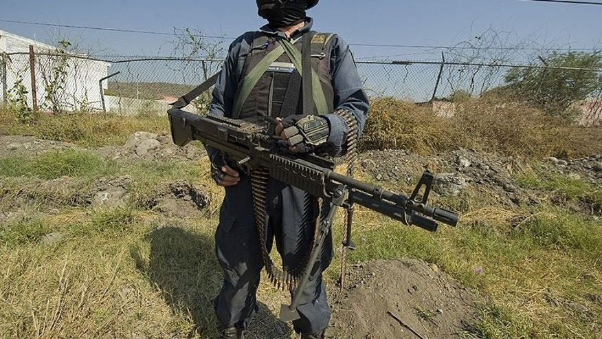 A Mexican policeman stands guard in Apatzingan, Michoacan State, on December 12, 2010. Heavily-armed men have assaulted Mexican federal police units in a carefully planned attack in which 22 people were killed in six towns, according to the government.