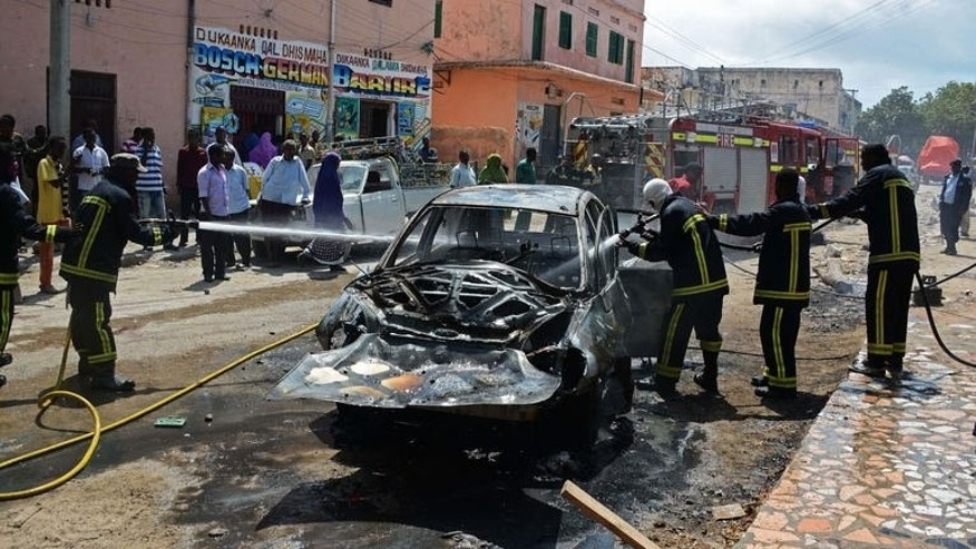 Firefighters extinguish a fire in a car after a bomb targeting a Somali MP exploded at Hamarweyne market in Mogadishu on July 24, 2013. At least one person was killed and several others were wounded Wednesday when the car bomb exploded in Somalia's capital, the latest in a string of attacks, police said.