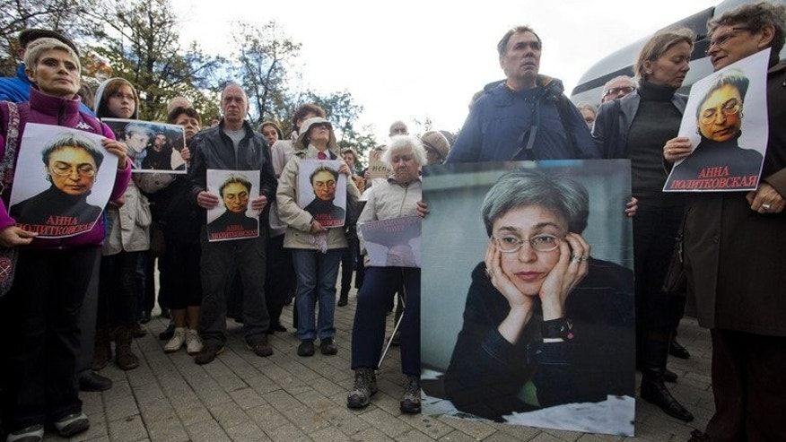 Demonstrators hold portrait of Anna Politkovskaya during a rally marking the sixth anniversary of her murder in Moscow, on October 7, 2012. A Russian jury has begun hearing the case against five men suspected over the murder of Politkovskaya, despite a boycott of the trial by her children and their lawyers.