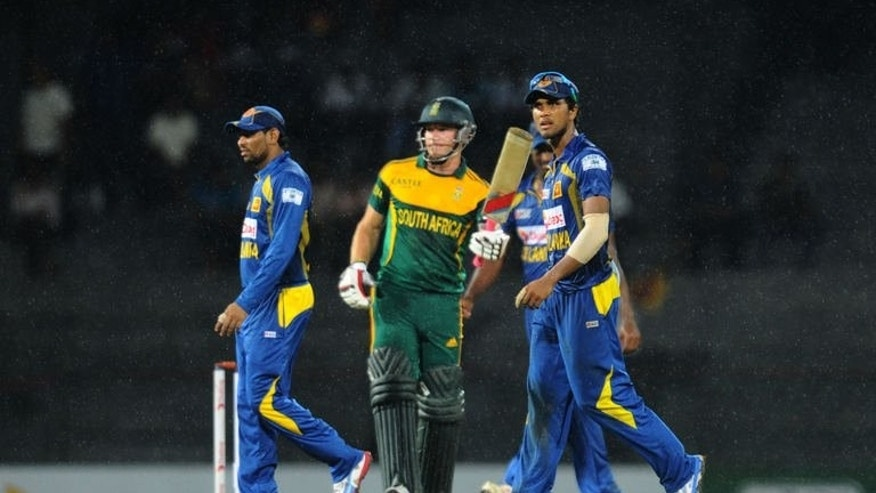 Sri Lankan captain Dinesh Chandimal (R) South African batsman David Miller (C) leave the pitch after rain stopped play during their match in Colombo on July 23, 2013. A groin injury to star batsman Hashim Amla has added to South Africa's woes as they attempt to prevent their limited-overs tour of Sri Lanka from falling apart.