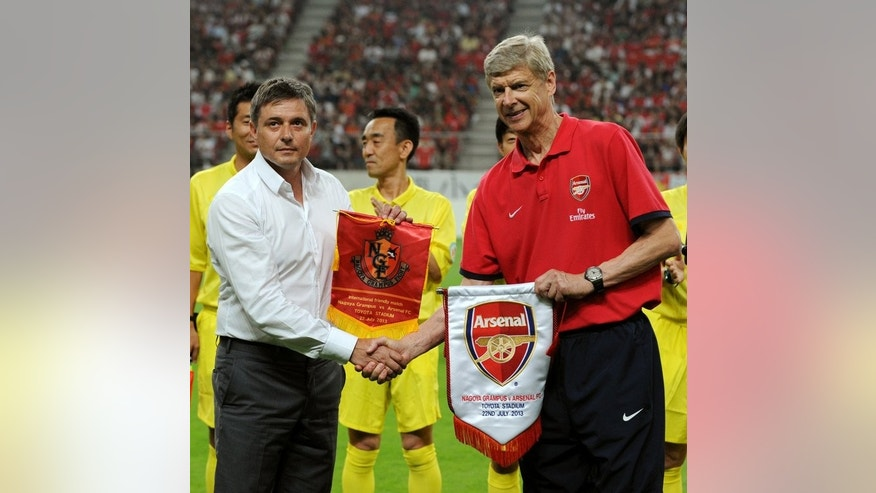 Nagoya Grampus coach Dragan Stojkovic (L) and Arsenal FC coach Arsene Wenger exchange their pennants prior to their friendly match in Toyota, Aichi prefecture on July 22, 2013.