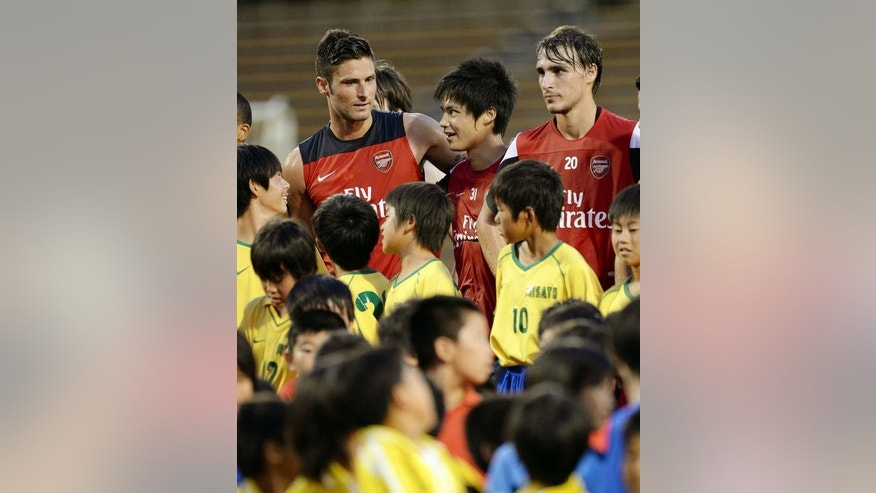 Arsenal players pose for photos with children prior to a soccer clinic in Nagoya on July 21, 2013.