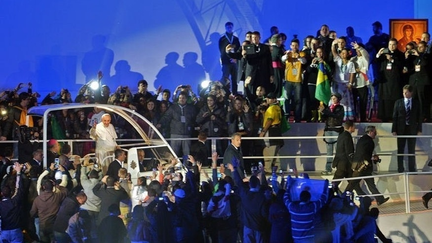 Pope Francis waves as he arrives in the popemobile at Rio de Janeiro's iconic Copacabana beachfront on July 25, 2013. A huge crowd of 1.5 million Catholics greeted Pope Francis on Brazil's Copacabana beach after the pontiff toured a notorious Rio slum to defend the cause of the poor.