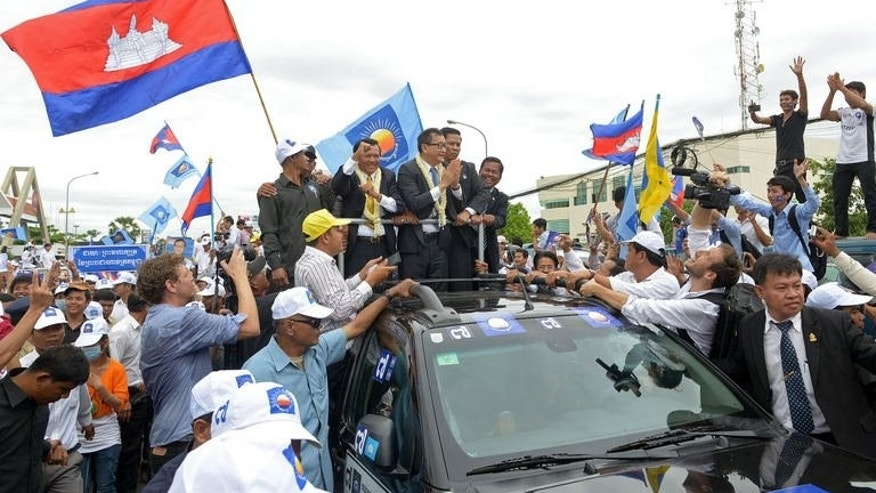 Cambodian opposition leader of the Cambodia National Rescue Party (CNRP) Sam Rainsy (centre R) greets supporters in Phnom Penh on July 19, 2013. Rainsy lost his bid to regain lawmaker status Thursday in a new setback to his efforts to challenge strongman premier Hun Sen in this weekend's election.