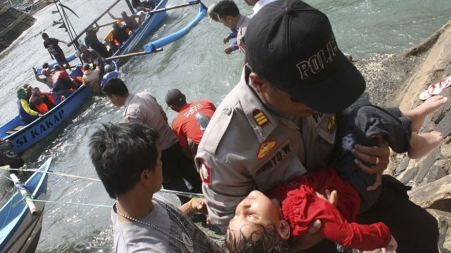 July 24, 2013: A police officer carries a child who appears to be unconscious after a boat carrying asylum seekers sank off Java island, in Cianjur, West Java, Indonesia. (AP Photo)