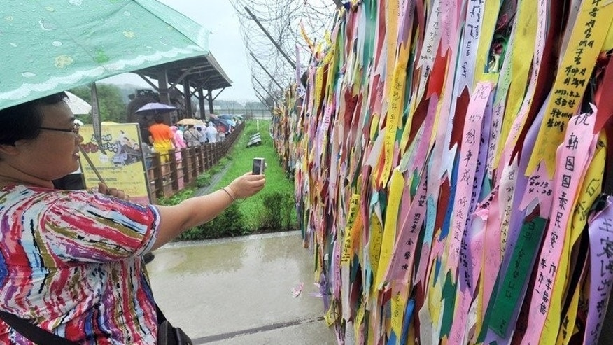 A tourist takes pictures of ribbons carrying messages wishing for the reunification of the two Koreas, at Imjingak peace park in Paju near the demilitarized zone dividing the two Koreas, July 23, 2013. Sixty years after the end of a war which killed millions and sealed the Korean peninsula's division into communist North and capitalist South, the dream of reunification is fading in South Korea.