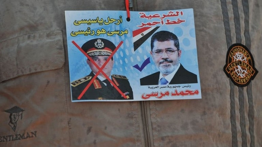 "A sticker on the shirt of a supporter of Egypt's ousted president Mohamed Morsi shows Morsi (R) with text above it reading in Arabic: ""Legitimacy is the red line"" and one of army chief Abdel Fattah al-Sisi (L) with text above reading in Arabic: ""Leave Sisi, Morsi is the president"" outside Cairo's Rabaa al-Adawiya mosque on July 24, 2013."