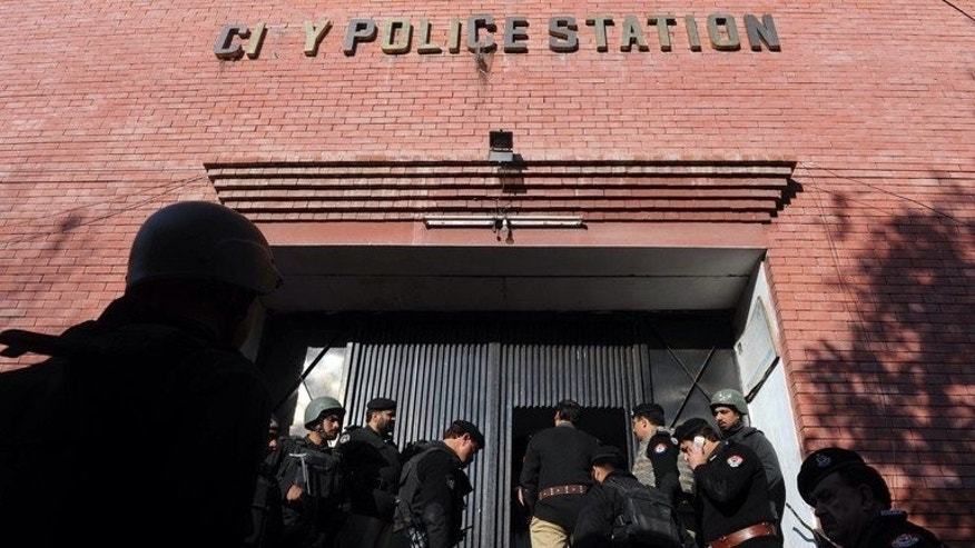 Pakistani officers enter a police station in Peshawar on February 24, 2012. Gunmen ambushed a senior police commander as he headed to work in Pakistan's northwestern city of Peshawar on Thursday, seriously wounding him and killing his bodyguard and driver, officials said.