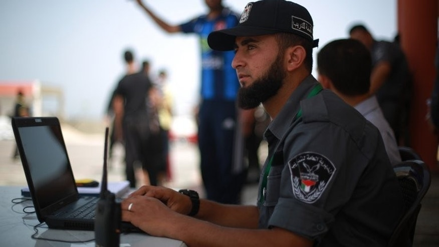 "A Hamas policeman sits at his laptop in Gaza City on June 2, 2013. Authorities in the Hamas-ruled Gaza Strip on Thursday closed local offices of Al-Arabiya TV and Palestinian news agency Maan for alleged ""false"" reporting of Hamas help for Egypt's Muslim Brotherhood."