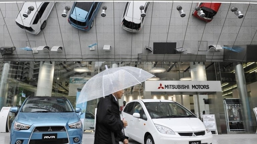 A man holding an umbrella walks past a showroom of Mitsubishi Motors Corp. in Tokyo on April 27, 2010. Mitsubishi Motors recalled more than 650,000 small cars sold in Japan over a possible fire risk.