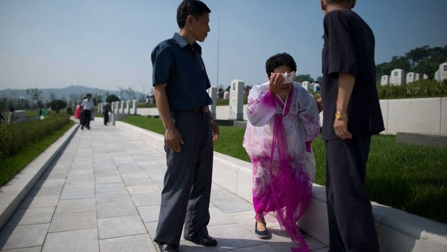 A woman cries during the inauguration of a Korean war military cemetery in Pyongyang on July 25, 2013. Selected remains of North Korean soldiers deemed to be heroes of the revolution were relocated from around the country to the new site.