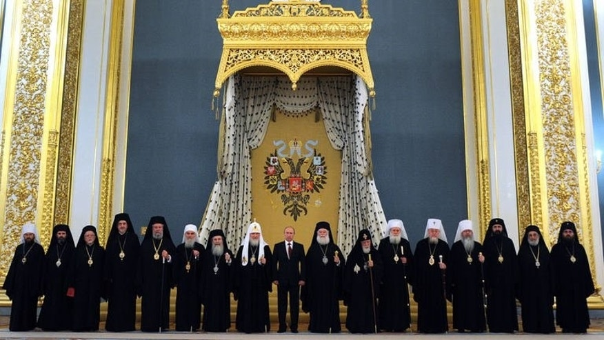 Russian President Vladimir Putin (C) poses for a family photo during the meeting with Orthodox leaders at the Kremlin in Moscow on July 25, 2013.