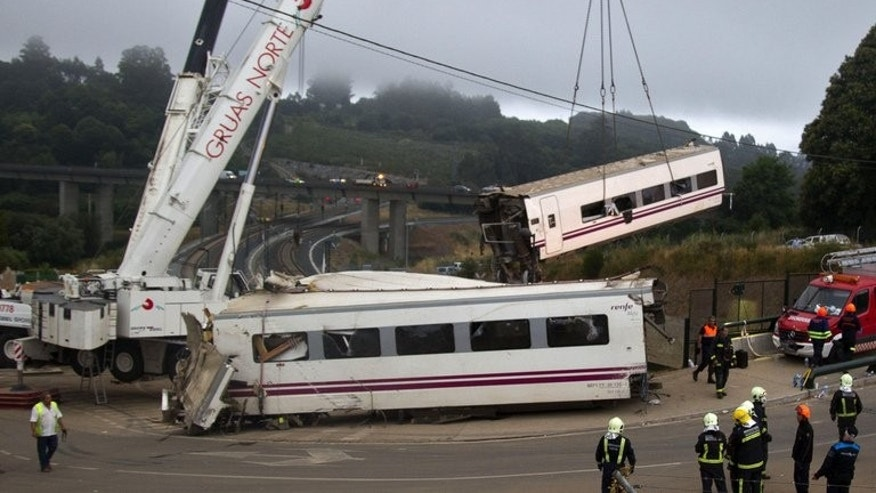 A crane removes a passenger car at the site of a train accident near the city of Santiago de Compostela on July 25, 2013. Spanish police were waiting Friday to question one of the drivers of the train that derailed, killing at least 80 passengers, amid media reports it was travelling at twice the speed limit.