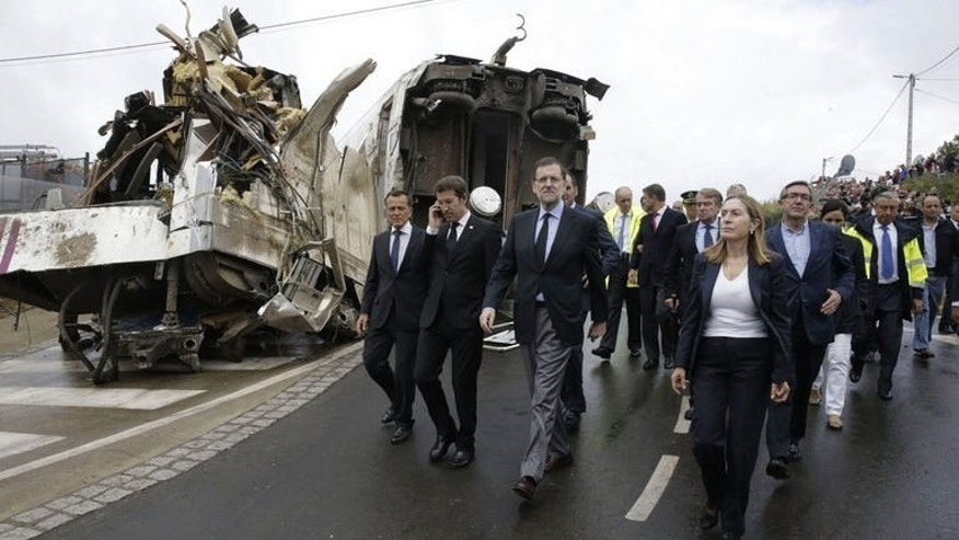 Spanish Prime Minister Mariano Rajoy (3rd L), Spanish Minister of Public Works and Transport Ana Pastor (front R), Galicia's regional President Alberto Nunez Feijoo (2nd L) visit the site of a train accident near Santiago de Compostela on July 25, 2013. Police were waiting Friday to question one of the drivers of the train that derailed, killing at least 80 passengers
