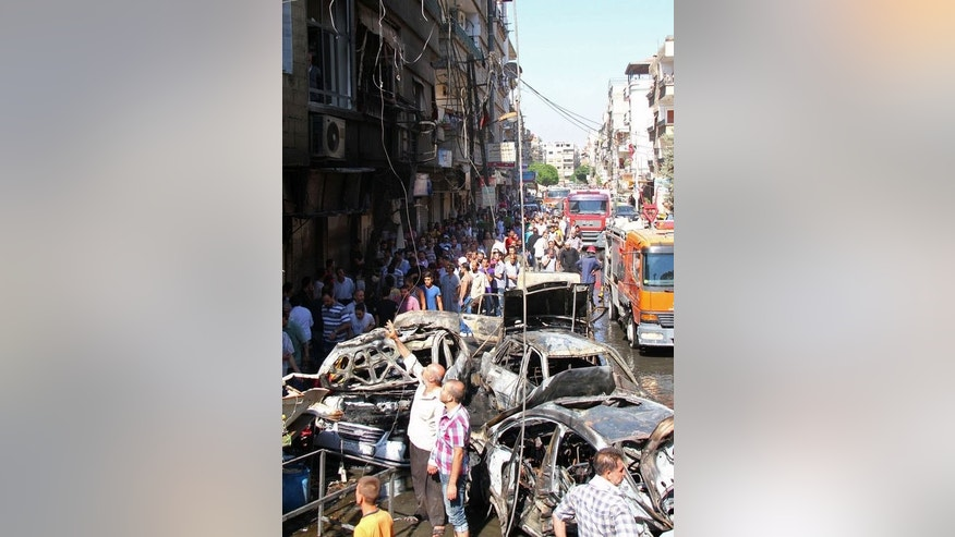A handout picture released by the Syrian Arab News Agency (SANA) shows Syrians looking at the aftermath of an attack on July 25, 2013 in the suburb of Jaramana in southeast Damascus.