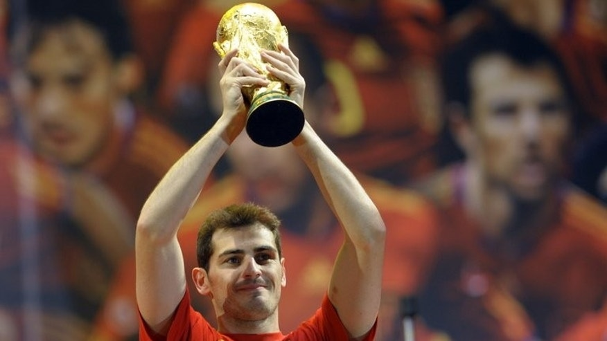 "Spain's goalkeeper Iker Casillas holds up FIFA World Cup 2010 trophy in Madrid on July 12, 2010. Sepp Blatter's plans to move the 2022 World Cup in Qatar to the winter would spark global ""chaos"", Premier League chief executive Richard Scudamore said."
