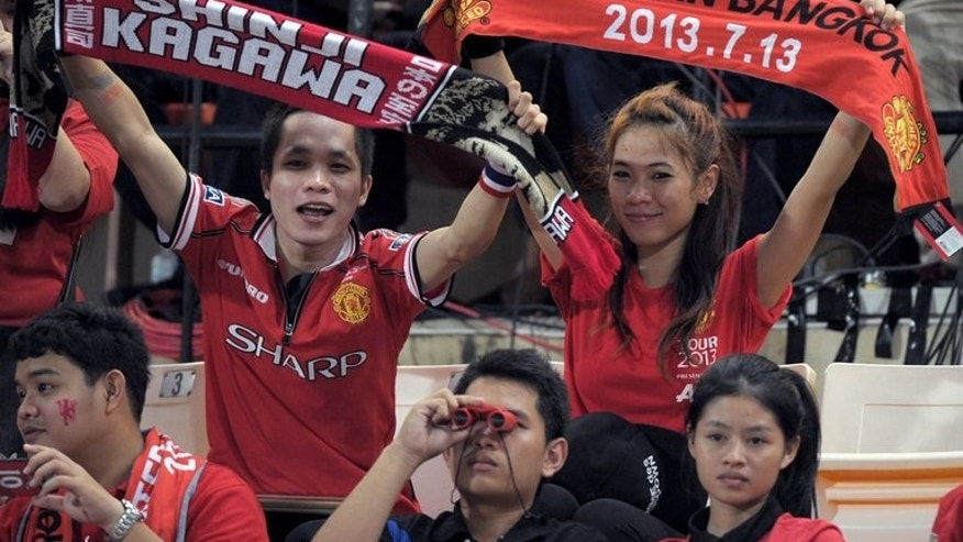Manchester United fans watch an exhibition match against the Singha All Stars in Bangkok on July 13. David Moyes, newly appointed as Manchester United's manager, was amazed at the welcome when he stepped off their chartered jet in Bangkok, comparing it to Beatlemania.