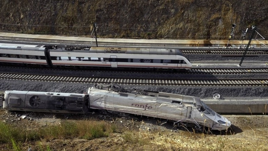 A train passes the scene of a train derailment at Angrois, near Santiago de Compostela, northwestern Spain, on July 26, 2013. The driver of the fast-moving train that flew off the tracks, killing at least 80 people, was unable to break in time, newspaper El Pais reported Friday.