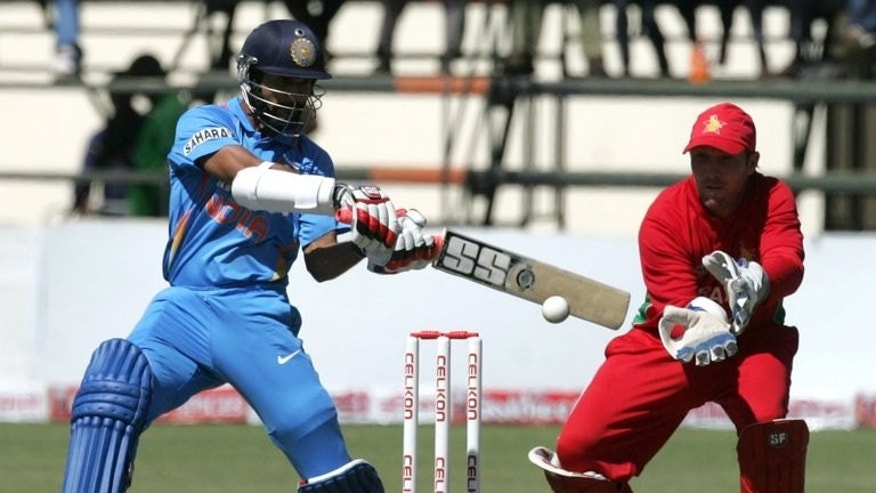 India's batsman Shikhar Dhawan (L) and Zimbabwe's captain Brendan Taylor, seen in action during the 2nd match of their 5-match ODI series, at Harare Sports Club, on July 26, 2013.