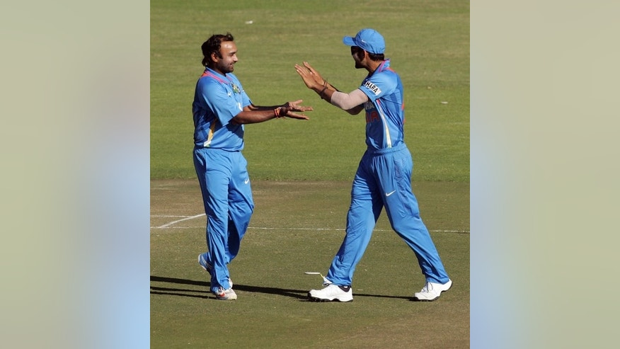 Amit Mishra (left) celebrates a wicket with Virat Kohli against Zimbabwe at Harare Sports Club on Friday. The hosts dismissed Rohit Sharma and Virat Kohli in the opening 10 overs, but Shikhar Dhawan led a charmed life as he was caught off a Kyle Jarvis no-ball, dropped by wicketkeeper Brendan Taylor when he was on just 14 and then put down again when he was on 70.